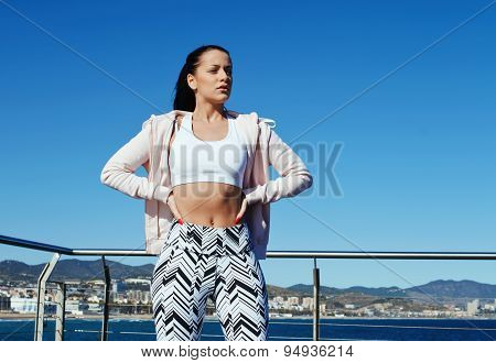 Female runner taking break after fitness training outdoors while standing with hands on her hips