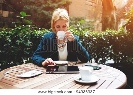 Businesswoman at coffee time working on digital tablet while sitting on the terrace of coffee shop
