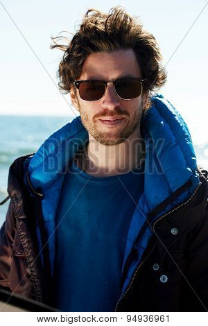 Handsome man standing outdoors cold sunny day on north arctic sea promenade on the beach