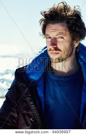 Portrait of young traveler hipster man dressed in winter jacket looking to the camera cold sunny day