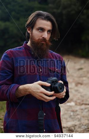 Hipster tourist checking out the sights in nature landscape holding his professional camera
