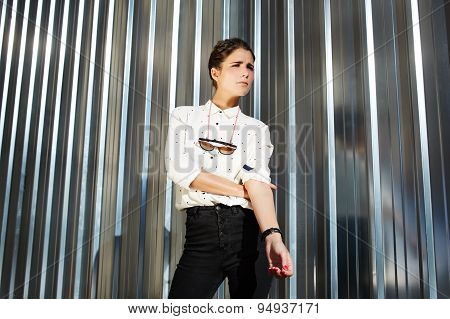 Attractive fashionable  brunette hipster woman posing on shiny wall background while looking away