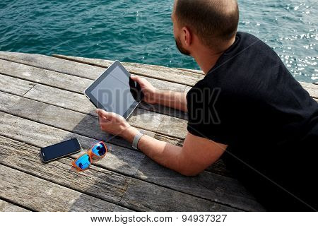 Young man relaxing and enjoying outdoors while reading digital e-book on touchpad