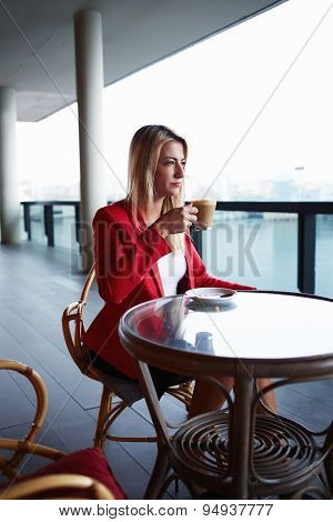 Attractive businesswoman on a coffee break sitting at coffee shop table looking pensive and focused