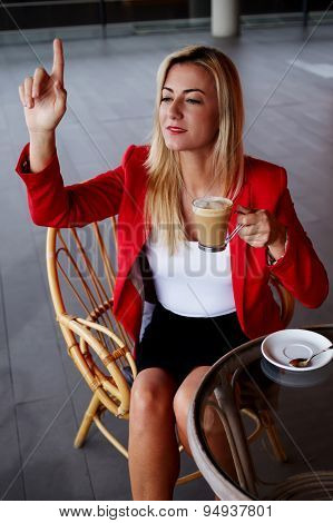 Elegant businesswoman calling for waiter while sitting at coffee shop during lunch break