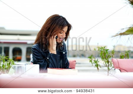 Portrait of gorgeous young woman talking on mobile phone while sitting in restaurant terrace