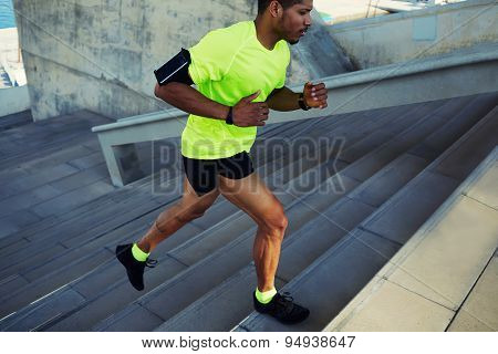 Sporty young man in fluorescent t-shirt training or working out outdoors while jogging up the steps