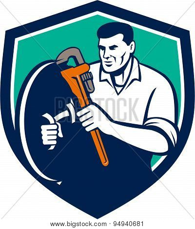 Illustration of a plumber holding brandishing monkey wrench set inside shield crest on isolated background done in retro style. poster