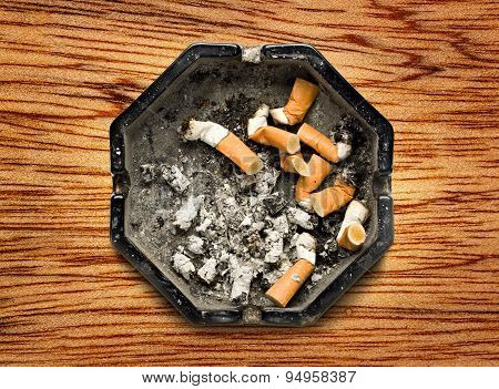 Black ashtray with cigarette stubs in closeup poster
