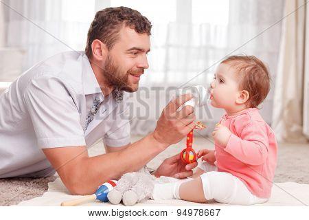 Nice father feeding his baby
