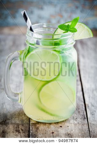 homemade lemonade with lime mint in a mason jar on a wooden rustic table poster