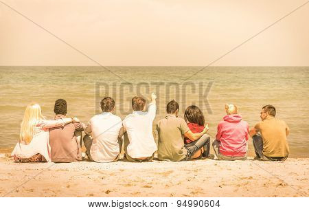 Group Of International Multiracial Friends Sitting At The Beach Talking With Each Other