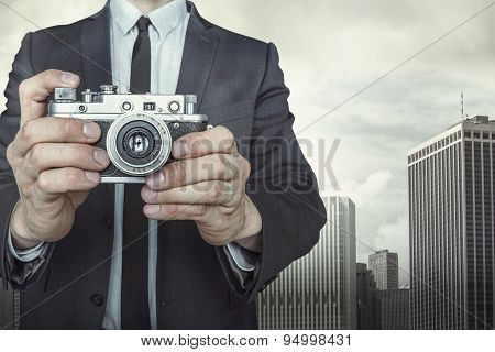 Businessman taking a photo with vintage camera