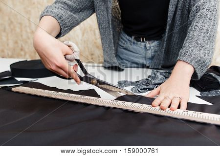 Tailor cutting out dark fabric with large scissors on the workbench in his shop. Close-up of female hands working with shears. Clothes making process