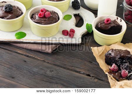 Chocolate cakes with raspberries on a dark wooden table with free place for your object