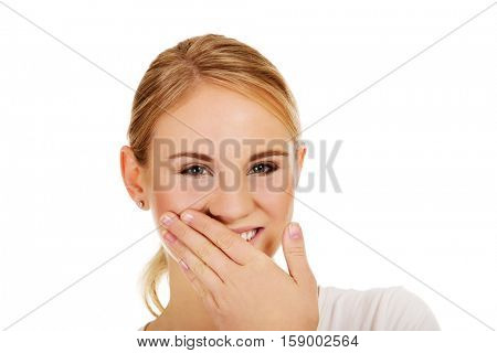 Young woman giggles covering her mouth with hand.