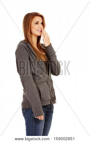 Giggles teenage woman covering her mouth with hand.