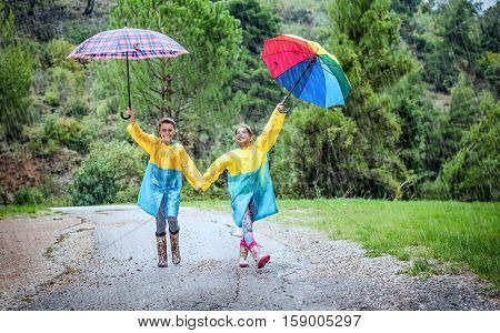 Children with colorful rainbow umbrellaraincoats and waterproof boots play in the rain