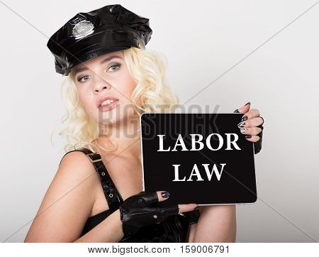 labor law written on screen. beautiful female police officer holding pc tablet.