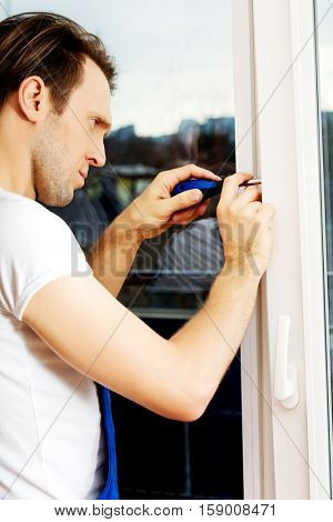 Young handyman repair window with screwdriver