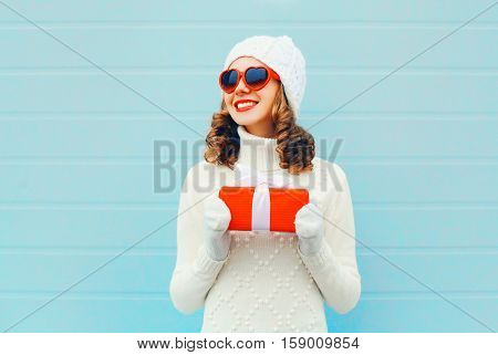 Christmas Portrait Happy Smiling Woman With Gift Box Wearing A Knitted Hat Sweater Over Blue Backgro