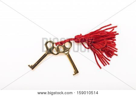 Two skeleton keys on a red tassel against a white background against a white background
