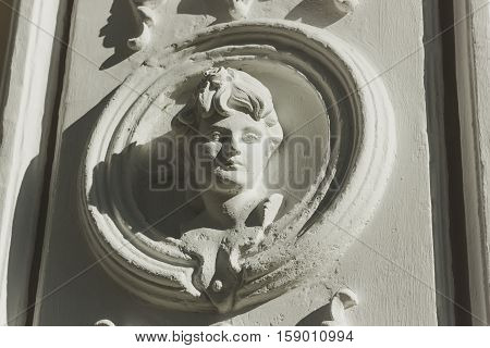 The bas-relief with the image of a young woman on a facade