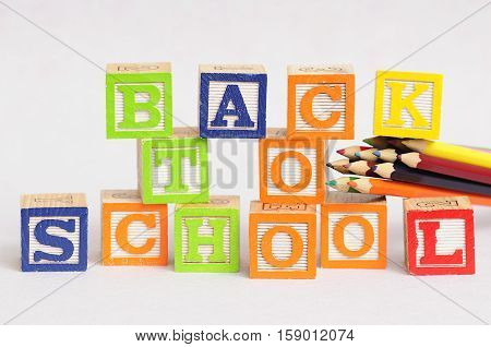 Back to school spelled with alphabet blocks displayed with coloring pencils on a black background