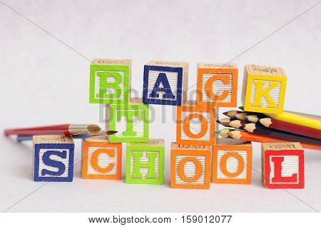 Back to school spelled with alphabet blocks displayed with coloring pencils and paintbrushes on a white background