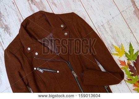 Brown cashmere coat autumn wooden background autumn leaves. Fashion concept.