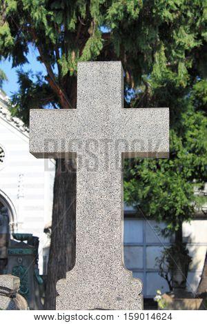 Closeup viw of a cross gravestone in a graveyard