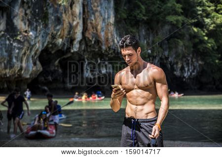Half body shot of a handsome young man using cell phone, standing on a beach in Phuket Island, Thailand, shirtless wearing boxer shorts, showing muscular fit body