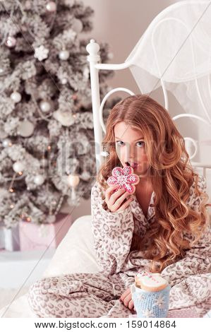 Beautiful blonde teen girl 8-10 year old biting gingerbread drinking tea sitting in bed in room over Christmas tree. Celebration. Christmas eve. Looking at camera.