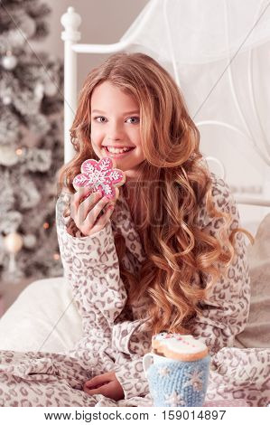 Smiling beautiful blonde teen girl 12-14 year old holding gingerbread and drinking tea in bed. Christmas tree. Holiday time. Celebration.