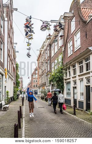 Amsterdam Netherlands - August 2 2016: Boy jumping trying to reach hanging shoes in a street in historical city center of Amsterdam.