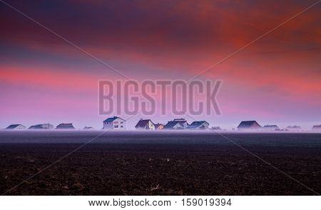 Rural house in the fog on a background of the morning sky