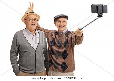 Elderly man pranking another man with bunny ears and taking a selfie with a stick isolated on white background