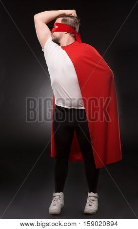 Egoist or selfish super hero man posing isolated on grey background. Handsome man with red mask on kissing his biceps in studio.