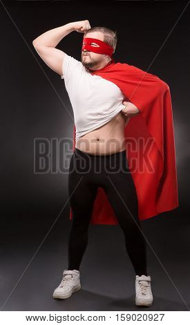 Handsome man with red mask on in super hero costume. Super hero man showing his strong body isolated on black background. Super hero man ready to help world.