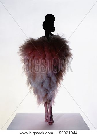 Art fashion studio photo of beautiful elegant woman in luxury evening dress. Drawing of shadows and light. Light and color effects. Fashion style