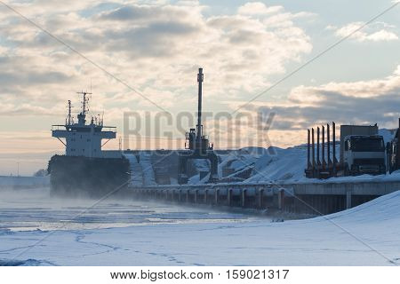 Industrial winter lanscape of bulker in a Harbour, loading wood.