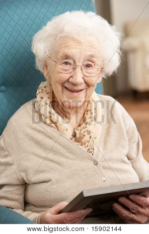 Senior Woman Looking At Photograph In Frame