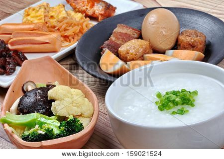 Close up of rice gruel with dish of sausage spicy clams ,sweet radish omelet and spicy caned mackerel and fried mixed vegetable and dish of stewed boiled egg.