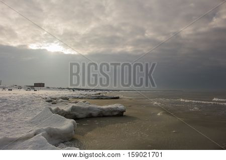 Beautiful winter landscape with snowy breakwater and ice