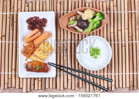 Rice gruel served with dish of sausage spicy clams ,sweet radish ,omelet and spicy caned mackerel and fried mixed vegetable.