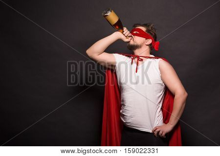 Super anti hero man drinking alcohol while posing in studio. Handsome man drinking alcohol drinks while posing for photogrpher.