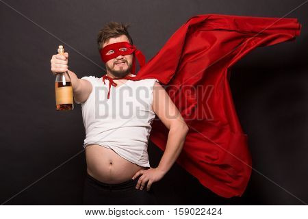 Super anti hero man showing bottle with wine or whiskey while drinking alcohol isolated on black background. Handsome man is bad man.