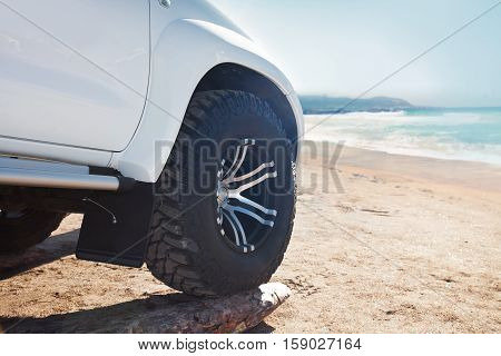 Close up of white car on the sand on a bright sunny day near the sea.