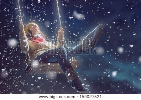 Beautiful young woman on a swing on snowy winter walk. Outdoor fun for winter vacation. Portrait girl on dark background.
