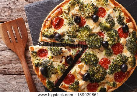 Savory Tart With Chicken, Broccoli, Tomatoes And Olives Close-up On The Table. Horizontal Top View